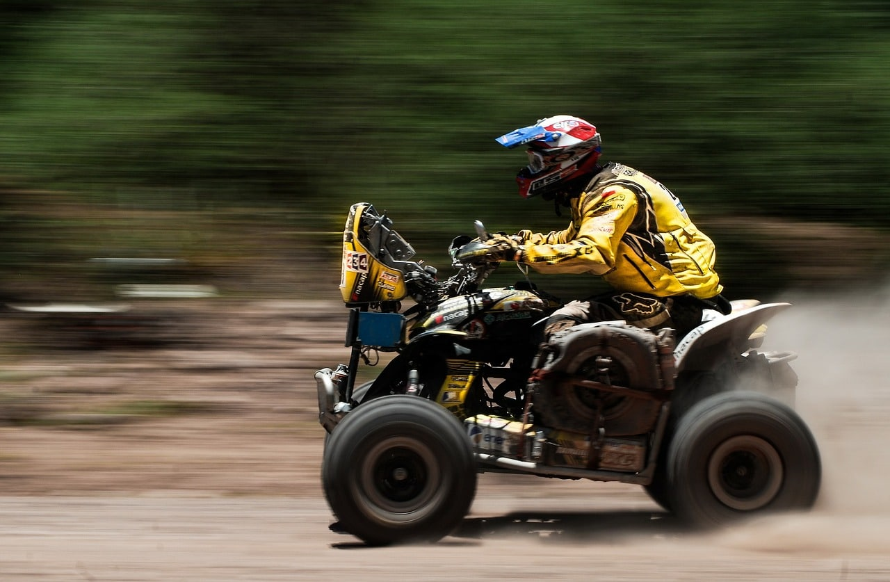 A man in yellow gear rides an ATV along a dirt track