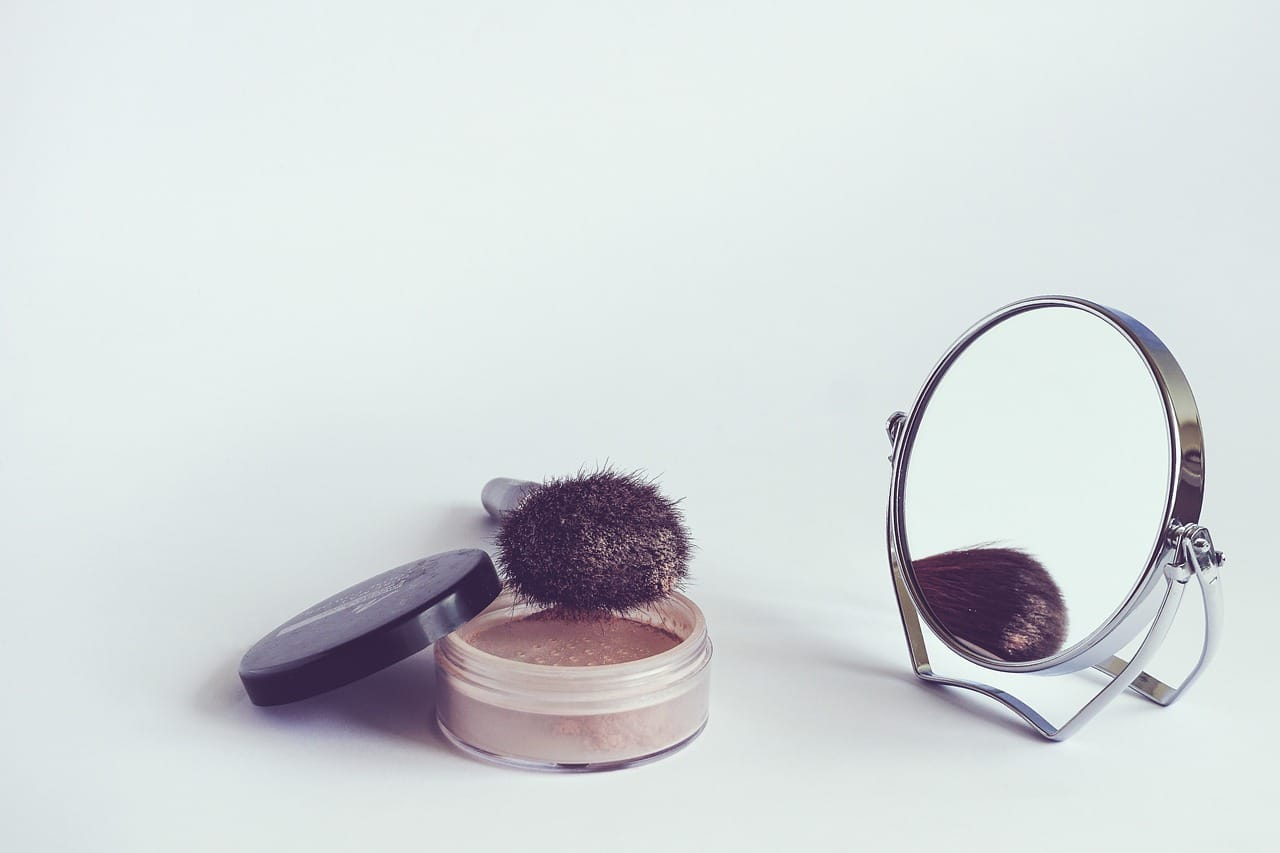 Powder foundation and brush set in front of a round table mirror