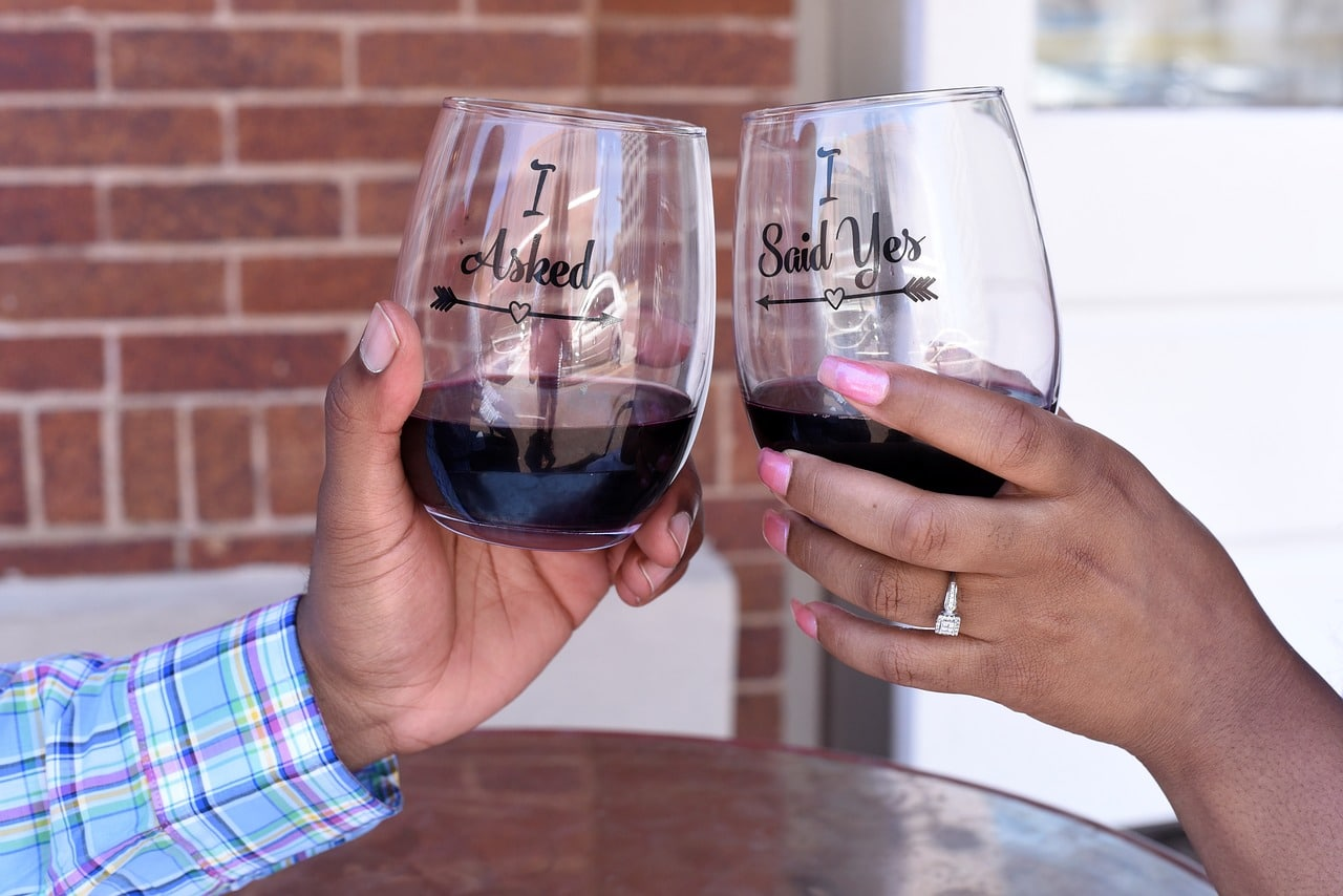 Newly engaged couple sip wine from decal glasses