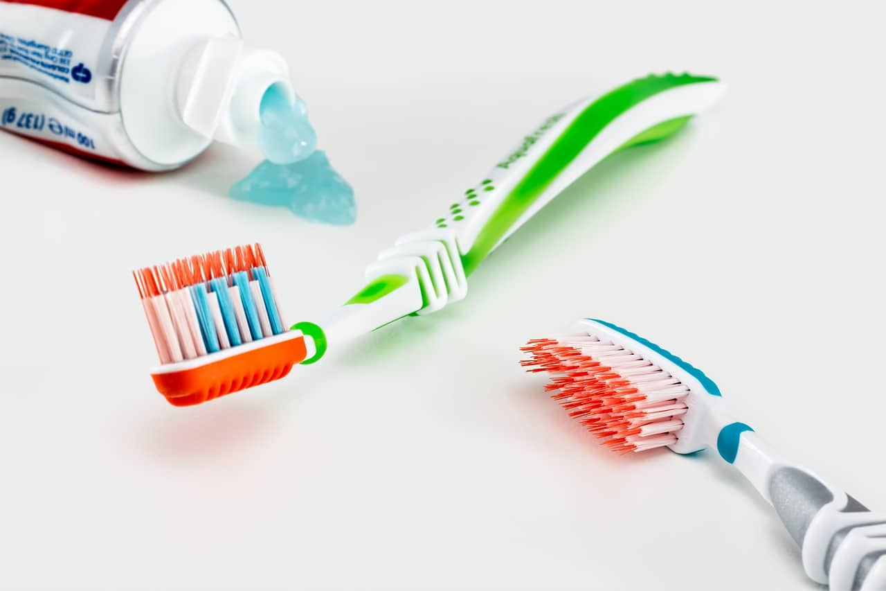 An opened tube of toothpaste sits beside two colorful toothbrushes
