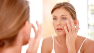 Woman applying moisturizer and looking at the mirror