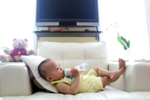 A baby lounges on a chair while drinking bottled formula