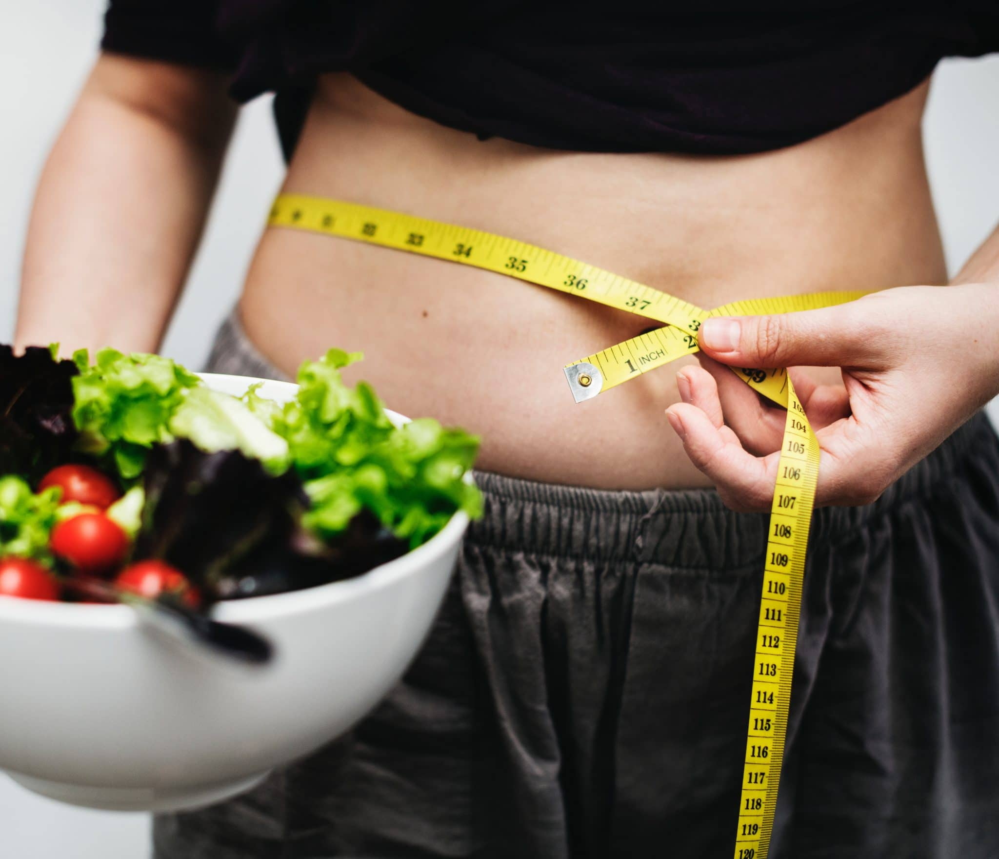 White woman holds a salad while using a yellow tape measure to measure her bare waist
