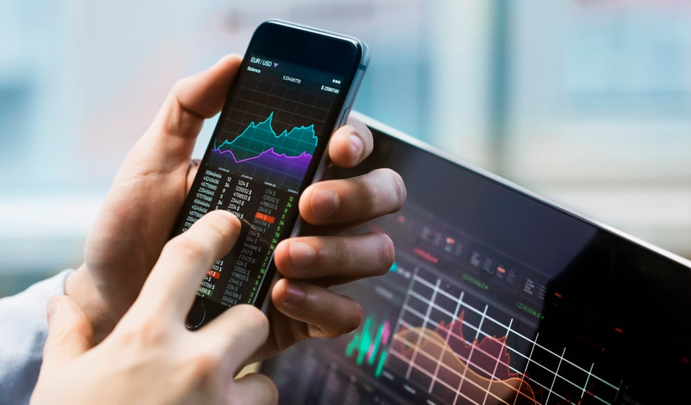 Business man holding phone with the best stock trading apps