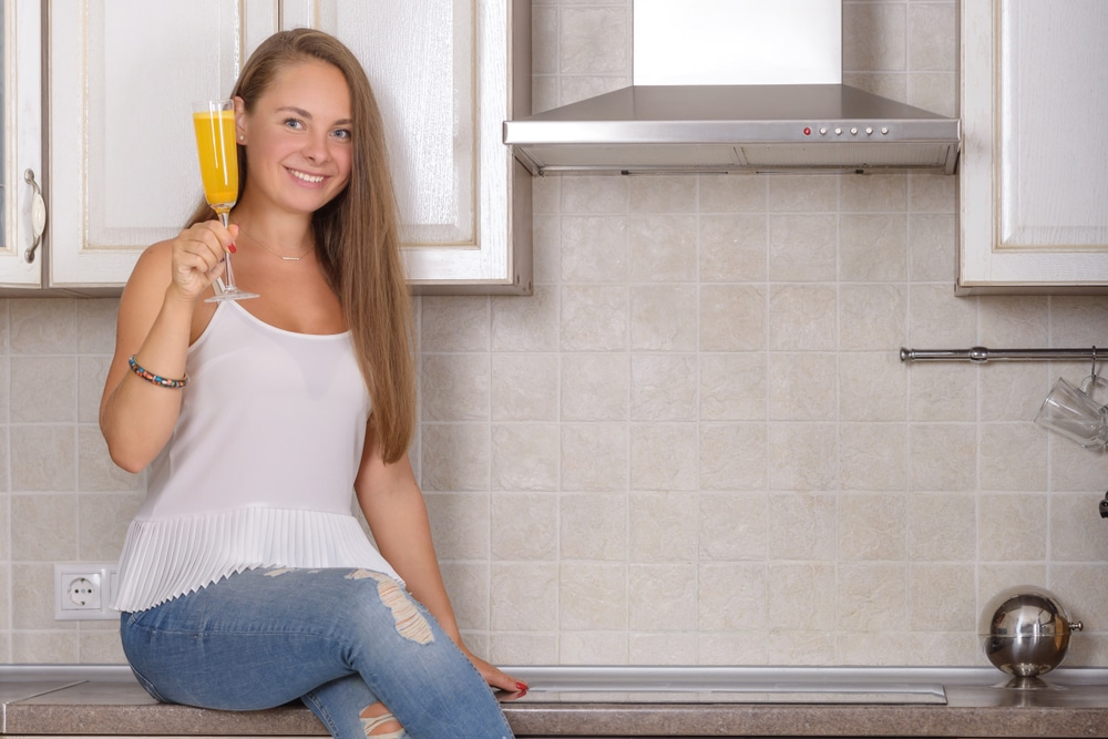Detox drink from turmeric in hands young woman in kitchen