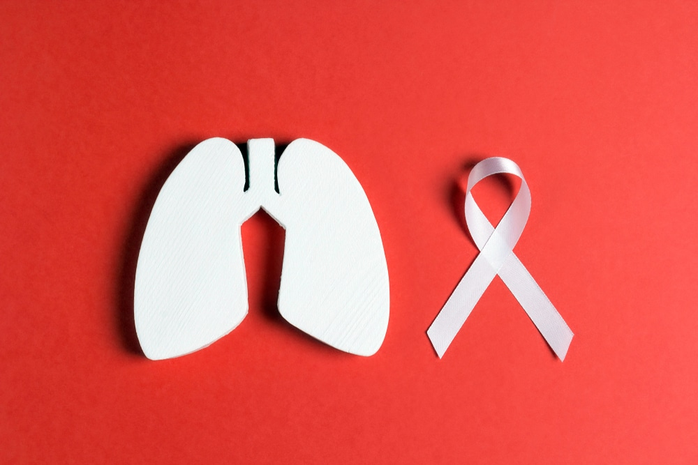 White lung cancer awareness ribbon and lung symbol on red background. November lung cancer awareness month. Healthcare and medicine concept.
