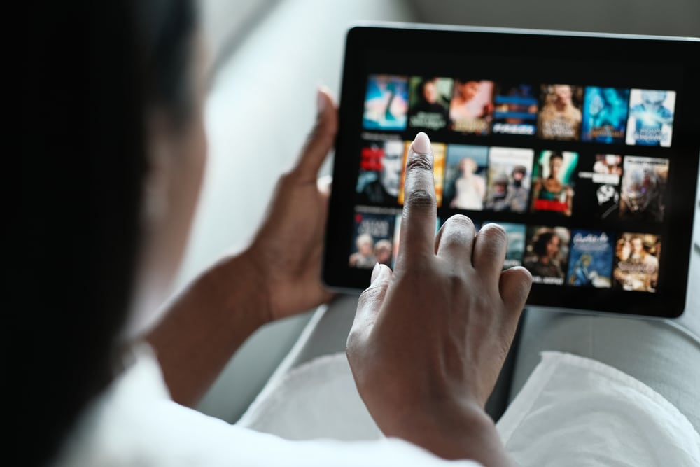 African American Woman Lying Down On Sofa At Home, Choosing Movie On Internet Streaming Service. Over The Shoulders.