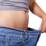 Thin woman tugs at loose pants