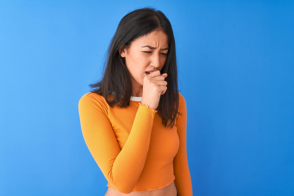 Young beautiful chinese woman wearing orange t-shirt standing over isolated blue background feeling unwell and coughing as symptom for cold or bronchitis. Healthcare concept.