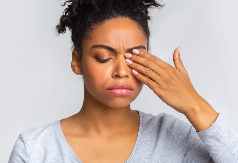African girl rubs her eye, suffering from conjunctivitis, ocular diseases concept