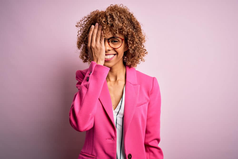 Young african american businesswoman wearing glasses standing over pink background covering one eye with hand, confident smile on face and surprise emotion.